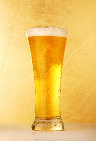 single beer: Glass of beer close-up over yellow background  Stock Photo
