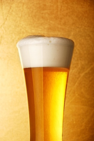 Glass of beer close-up over yellow background  Stock Photo