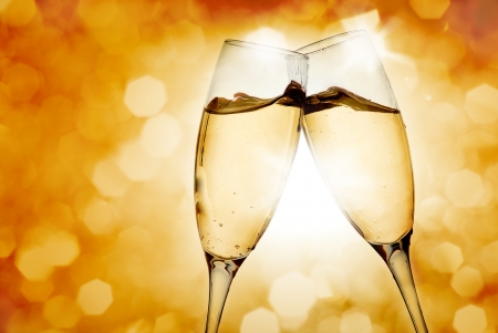 Two elegant champagne glasses on golden background photo