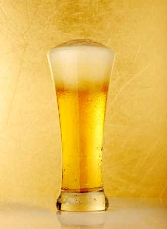 Glass of beer close-up over yellow background  photo