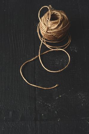 skein: Skein of jute twine on a dark wooden background Stock Photo