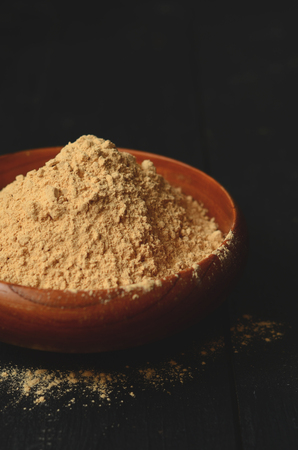 maca: Maca root powder in a wooden bowl