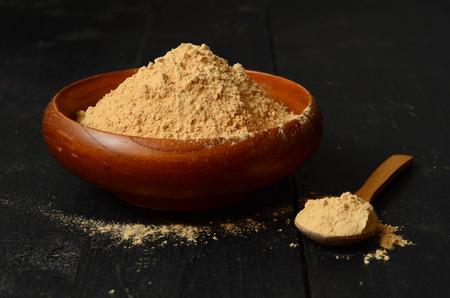 maca root: Maca root powder in a wooden bowl