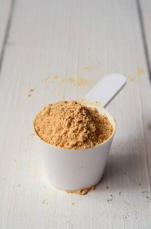 maca: maca root powder in a measuring scoop