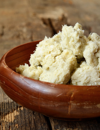 unrefined: Unrefined raw shea butter on wooden background Stock Photo