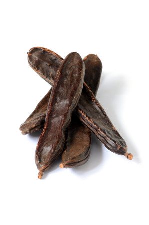 carob: Ripe carob pods, carob powder can be used as a substitute for cocoa Stock Photo