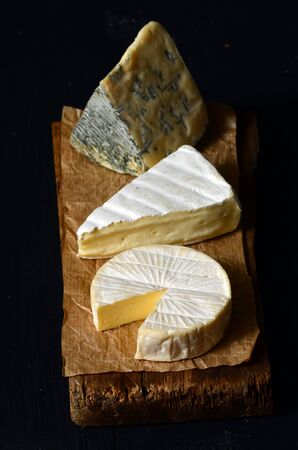 cheeseboard: Different kinds of cheeses: camembert, brie,  blue cheese