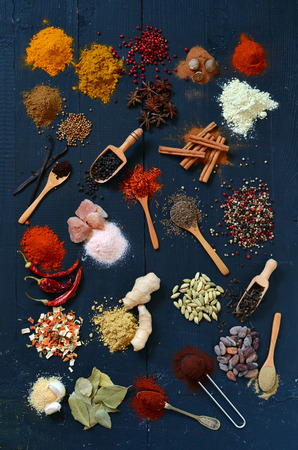 variability: Colorful spices and herbs on a dark wooden table