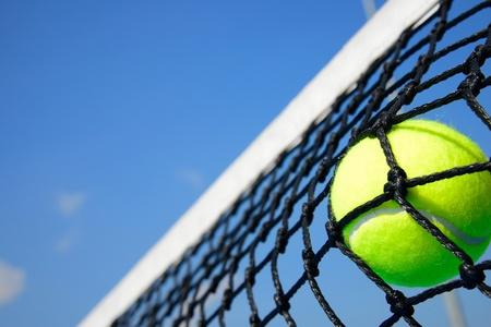 raqueta de tenis: Pelota de tenis en la red Foto de archivo