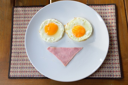 breakfast smiley face: breakfast smiley face with bacon and fried eggs on white plate