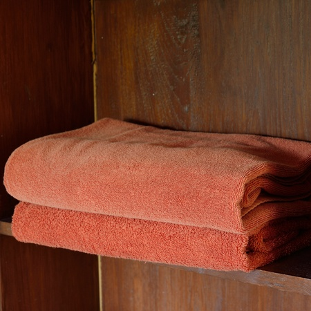 red towels on wooden shelf photo