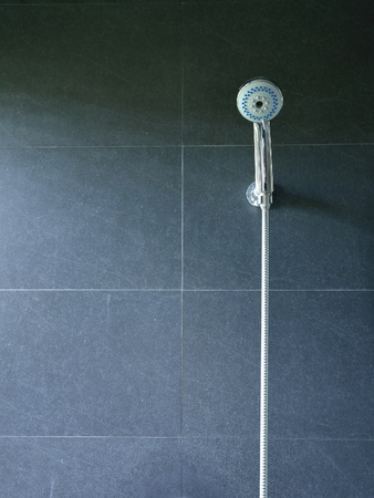 Bath shower on black tile wall photo