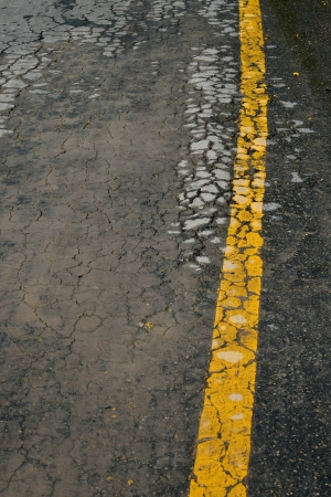 yellow line on asphalt road crack surface photo