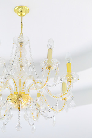 Luxury crystal chandelier on white wall background photo