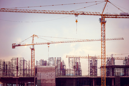 Construction site with cranes on sky background, retro tone image photo