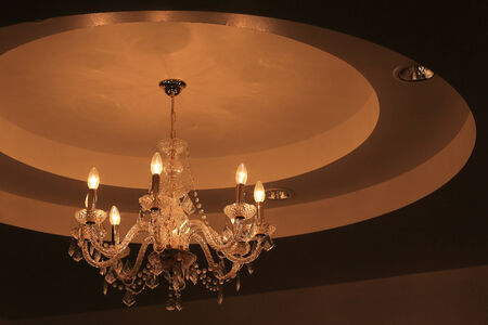 Luxury crystal chandelier on dark wall background photo