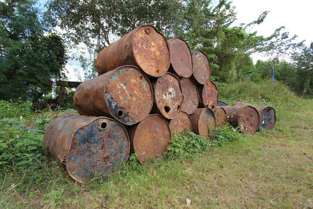 remediation: old rusty metal fuel tanks stacked in a row