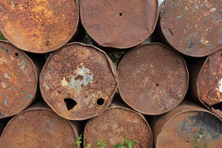 old rusty metal fuel tanks stacked in a row photo