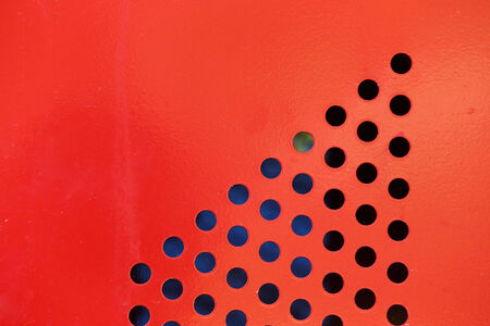 Background of red steel metal with circle perforated holes  photo