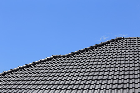 black tiles roof on a new house with blue sky photo