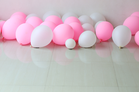 pink and white balloon on floor with white wall background photo