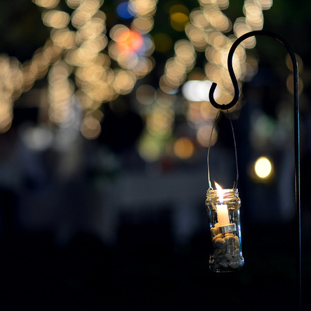 Candle light in glass jar decorated night garden Stock Photo