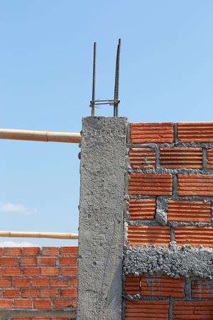 cement pole: brick wall and pole house in residential building construction site Stock Photo