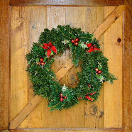 christmas wreath with decorations on wood door photo