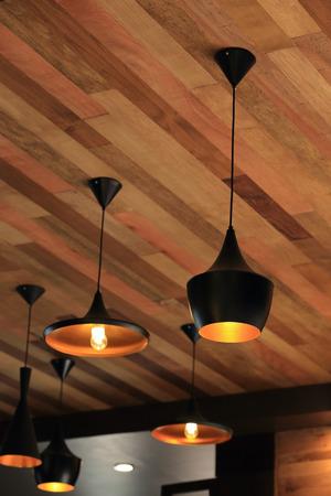 Lampada a sospensione nera sulla parete di legno del soffitto Archivio Fotografico - 32168787