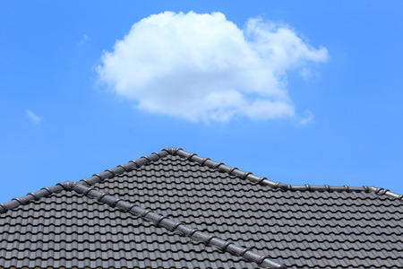 tile of roof: black tile roof on a new house with blue sky
