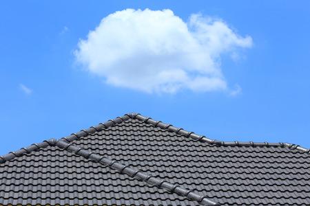 zwarte tegel dak op een nieuw huis met blauwe hemel
