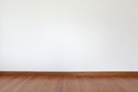 witte mortel muur en houten vloer in de kamer Stockfoto