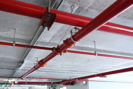 fire safety: red pipeline extinguishing water in industrial building