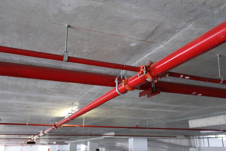 sprinkler alarm: red pipeline extinguishing water in industrial building