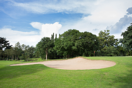 golf course with sand bunker and green grass photo