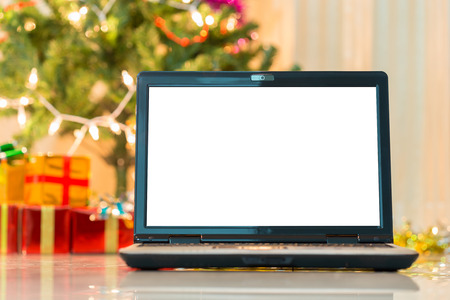 laptop with gift box and christmas lights background photo