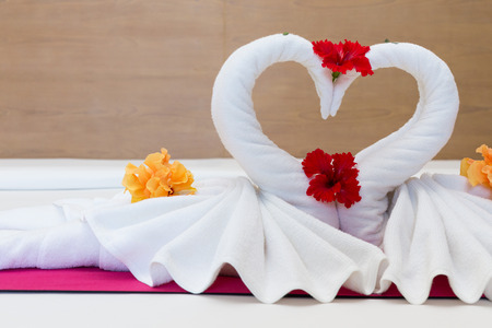 heart suite: white swans made from towels on bed in the hotel
