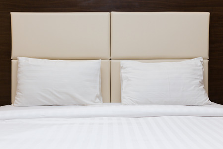 king size bed: white pillow and leather headboard in bedroom