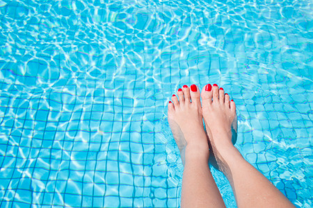 woman legs with red nail in swimming pool photo