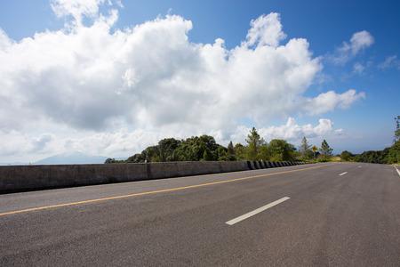 asphalt roadway with cloud blue sky background Stock Photo