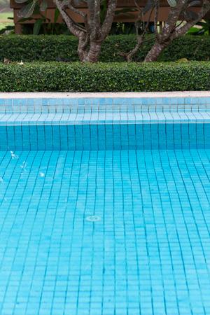 blue swimming pool in green garden photo