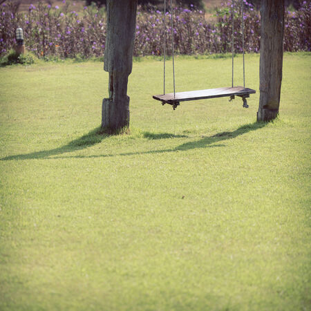 playground swing made wood hanging in green grass field photo