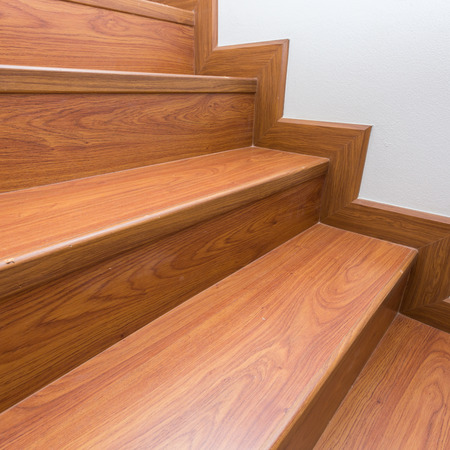 wooden staircase made from laminate wood in white modern house photo