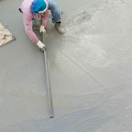 plasterer concrete cement worker plastering flooring of house construction photo