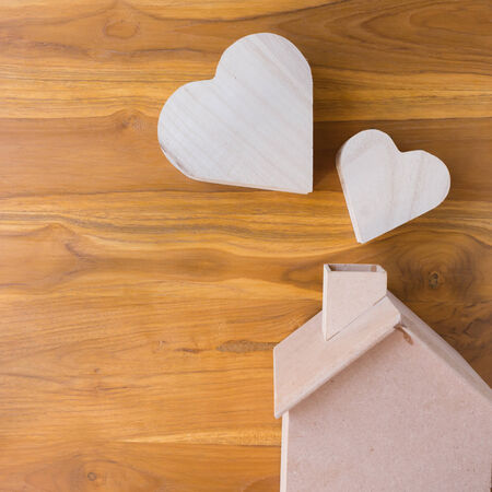 wooden house and heart on brown wood background photo