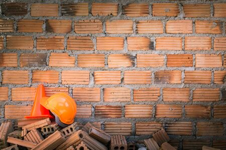 hard hat safety helmet in construction site with brick wall photo