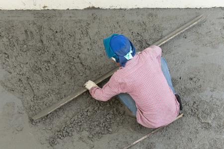 plasterer concrete cement worker plastering flooring of house construction 写真素材