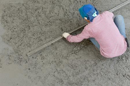 plasterer concrete cement worker plastering flooring of house construction photo