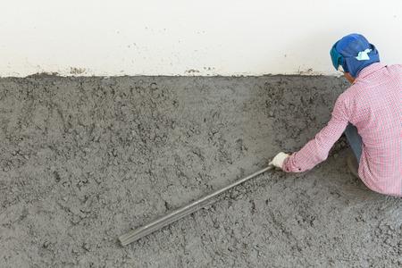 plasterwork: plasterer concrete cement worker plastering flooring of house construction Stock Photo