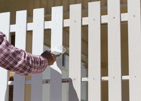 hand worker holding brush painting white on wood fence Stock Photo